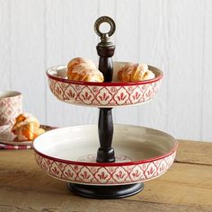 "RED FLOWER TWO-TIER EPERGNE -- Used with our Red Flower dinnerware or on its own, our two-tier epergne makes a very stylish server. Glazed clay with mango wood spindle and metal finial. Imported. Catalog exclusive. Minor assembly required. 13"" dia. x 15-1/2""H."