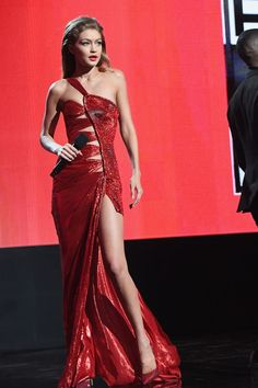 - Shecomplemented askin-tight red Atelier Versace dress with blown-back vintage waves,a brown smoky eye and bright coral lip.