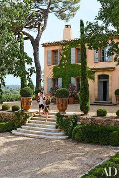Stor entréyta nära husnivå, mur med växtlighet framför, bred trappa ner till infart och parkering.