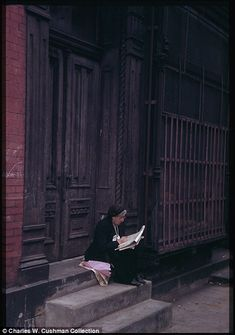 a woman, right, sits in front of a doorway in the Lower East Side, October 1942