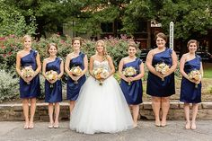 Blue and White Wedding Ideas - The bride and her bridesmaids | Navy one-shoulder bridesmaid dresses from David's Bridal | Photo by Amy Allen Photography | Downtown Modern Wedding on heartlovealways.com