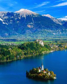 Lake Bled with little island and castle on the cliff in background.
