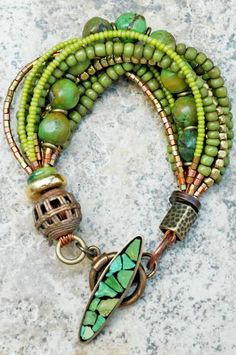 Green Turquoise & Bronze Bracelet: Elegant and earthy at the same time, this exotic green turquoise bracelet is a gorgeous piece of art-to-wear jewelry! A single strand of stunning green turquoise is combined with several strands of olive green glass from Indonesia, lime green glass from the Czech Republic, brass,