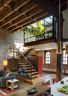 A custom steel stair repurposes timbers from the old roof joists as treads and landings.