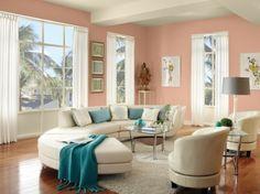 Barackszínű nappalifal korszerű félkör alakú ülőgarnitúrával. A visszafogott hangulatot ez esetben is türkizkék kiegészítők pezsdítik.