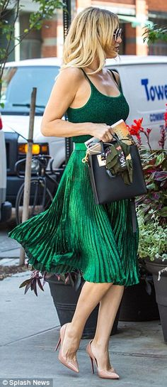 Shining star: Kate wore a fitted sleeveless shirt with a shimmering pleated skirt...