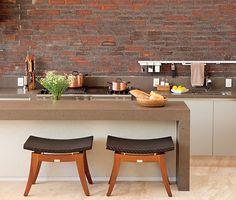 Aberta para a área externa, esta cozinha gourmet recebeu acabamento igual ao da fachada da casa. O arquiteto João Armentano cobriu as paredes com tijolos estilo inglês