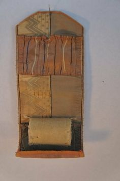 """1840 silk sewing roll house wife, early and nice.  Has 2 pockets and middle area for pins and needles. Soft iridescent mauve and grayish green; 7"""" long and 3"""" wide."""
