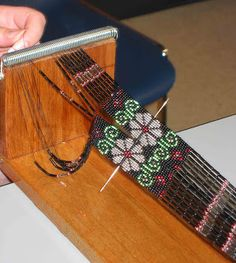 A loomed gerdan (Ukrainian traditional beaded necklace) in progress on its loom. Maria's father in law made these looms out of unstained mahogany door-jambs, springs and screws. I have one and treasure it.
