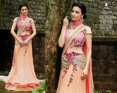 A pre-stiched sari in soft pink and cream portraying a contemporary spirit. 'Parsi' and 'zari' motifs with shades of pink in the blouse. Beautiful layers of jacquard net and brocade. Intricate handwork and ornate 'Parsi' embellishments at the waist