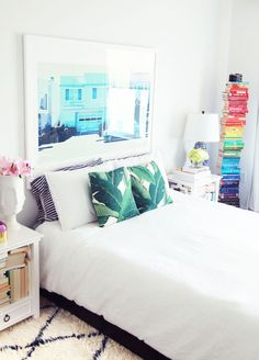 A headboard is a great way to visually frame up your bedroom. But the thing is, your headboard doesn't have to be a headboard at all. An oversized piece of framed art can do the same work for you, giving your bedroom or guest room tons of unique style in the process.