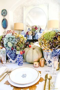 Elegant Heirloom Thanksgiving Table Scape - Randi Garrett Design with blue, purple and white hydrangeas, blue ginger jars, and green heirloom pumpkins. Monogram plates and gold flatware, stemware, chargers, and votives.