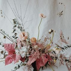 A beautiful Winter bouquet of styled wedding flowers. Masterfully created wedding decoration in beautiful red, pink and blush colors, composed of leaves, flowers and twigs. A beautiful composition and floral arrangement.