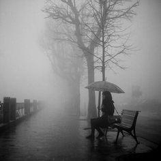 Waiting on park bench + raining + alone + hazy +  someone appears