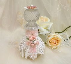 Altered bottle, shabby chic bottle . Decorated with pretty lace, hand dyed mulberry roses, handmade crystal bead embellishment, seam binding, pearl trim, lace doily and jewellery pice on top.