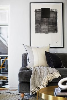 Masculine inspired living space with a monochrome palette, framed art, and a gray sofa