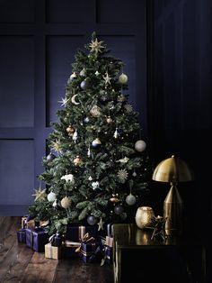 christmas tree inspiration This dramatic Christmas tree decoration idea has us all starry eyed. Stars, moons and luxe baubles come to life in a palette of inky blues and shimmering metallics.