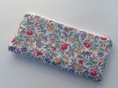 This pretty pouch is made with Liberty of London fabric and lined with a light gray floral cotton. Polyester fleece is sewn in to give it a bit of body. Closes with a white zipper. Dimensions 8 inches wide by 4 inches tall Uses Pencil case Cosmetic case Wallet This item is ready to ship now