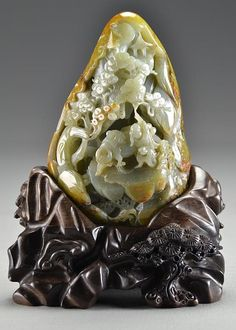 """Chinese Carved Jade Boulder on Stand  Finely carved to depict a scholar with two boys and a water buffalo beneath an ancient tree, the stone an even celedon and retaining most of it's original russet skin, raised on carved hardwood stand, 8.75""""H including stand, jade weighs 3.5lbs."""