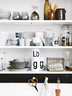 Regalböden statt oder zwischen Oberschränken sind eine lässige und leicht zugängliche Stauraumlösung für die Küche. Vorausgesetzt, Kleinkram verschwindet in Dosen und Körben.