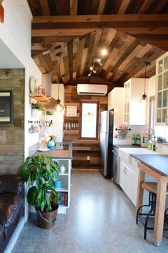 The tiny house features two vintage stained glass windows, white shiplap walls, and a barn wood ceiling and accent walls.