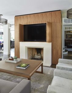 Morgante Wilson designed a  multi-functional living room  with seating to view the fireplace and a tv which is hidden within the fireplace.