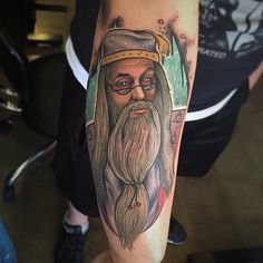 Cartoon like detailed and colored on forearm tattoo of Dumbledore