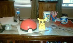 Pikachu and a Pokeball. This guy was a lot of fun. the pokeball is vanilla ice cream surrounded by chocolate cake w/ chocolate icing, then covered in fondant, and pikachu is sculpted from a blend of solid milk chocolate and rice krispies, also covered in fondant.