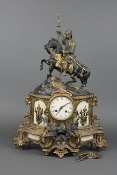 """Lot 701, A Victorian French 8 day striking figural mantel clock with enamelled dial and Roman numerals, contained in a gilt metal case surmounted by a figure of a crusader on horse back with pennant and above various military trophies 22 1/2""""h, estimate £200-300"""