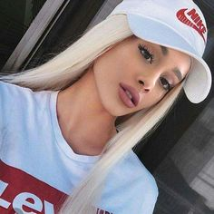 Ariana GRande wearing White & Red Nike Hat and Faded Blue Levis Shirt. her long hair is light blonde.:).