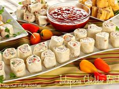 Jalapeno Cheddar Roll Ups  8 oz	Cream Cheese, softened 1 cup	Sour Cream 1× 15-oz can	Refried Beans 1× 15-oz can	Diced Tomatoes With Green Chilies, drained 8 oz	Monterey Jack/colby Cheese Blend 2.25 oz sliced	Ripe Olives, drained and patted dry 6	Green Onions, sliced thin ½	Red Bell Pepper, diced ⅓ cup	Chopped Fresh Cilantro 9	Jalapeno Cheddar Wraps or Large Tortillas