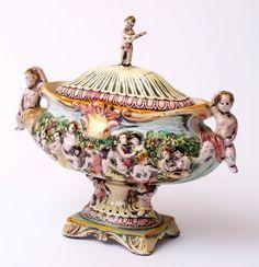 Terrine, CapodimonteAuf bewegtem, reliefiertem Sockel mit zwei Putti ovaler Korpus mit Figurengruppe — Porzellan