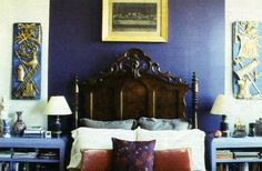 This master bedroom's headboard is striking against wall color.