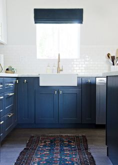White and navy kitchen design with glossy white tiled backsplash | The Vintage Rug Shop