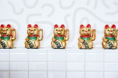 Sticking true to the name of this modern Asian restaurant, mini maneki-neko fortune cat figurines are displayed on a built-in shelf on the front of the white tiled service counter.