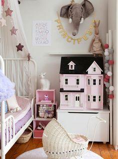 Metalowe lekkie łóżko ze zwiewnym baldachimem okazało się dobrym wyborem do niewielkiej dziecięcej sypialni. Ze względu na metraż pozostałe meble łączą różne funkcje – szafka jest jednocześnie miejscem przechowywania domku dla lalek, a różowe skrzynki ułożone w piramidę służą za stolik nocny. Jeśli chodzi o dekoracje, we wnętrzu dominują ozdobne girlandy poupinane w różnych miejscach.