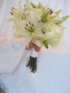 White bridal bouquet with lilies and roses.  www.fancyfloralsbynancy.com www.facebook.com/fancyfloralsbynancy