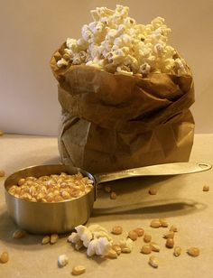 Pop popcorn kernels in the microwave in a brown paper bag.