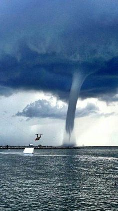 Quite a photo when the great waterski jump is barely noticed! (A great portrait shot would have been a close-up facial when s/he finally  looked back:)  Original PIN note: This water spout was in Florida... 13 of these in one day while sailing from the Gulf back into Marathon Key