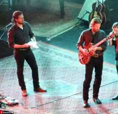 Spot the lead: Bradley Cooper and his body double  filmed A Star Is Born at the Greek Theatre in LA on Wednesday - but it was hard to say who was who. Hint: He's the one playing the guitar
