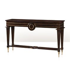 An imbuya burl console table, the rectangular top above two frieze drawers centred by a roundel and decorated with brass moulding, on tapering square legs joined by a shaped x stretcher, with brass peg feet. The original Mid Century Modern.