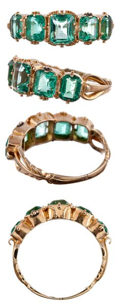 Antique Five Stone English Carved Emerald Yellow Gold Ring. A fine example of this celebrated and eternally beloved classic, with five emerald cut emeralds set in 18k yellow gold and finished with detailed shoulders. The emeralds weigh approximately 2.20 carats in total and are well=protected in this setting. This ring can be resized upon request. Via 1stdibs.