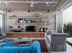 """Luis Andrade, a estante também é toda de concreto,  Ela foi executada na obra com formas de madeira e armação em ferro e fica camuflada na parede, que também é de concreto. O móvel de melamina no padrão amêndola rústica suaviza o visual duro do cimento. Para o arquiteto, móveis e outros elementos estáticos de concreto são sempre uma escolha estética aliada ao baixo custo, mas que devem ser previstas durante a construção ou reforma da casa, """"visto que é uma execução não tão simples e requer"""