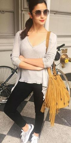 Alia Bhatt spotted in her casual self posing in grey V-neck top with leggings which she clubbed with oversize fringe bag and metallic sneakers. Shop this look on Huew.