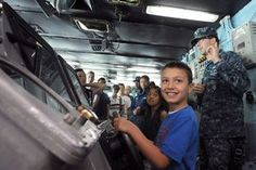 Mass Communication Specialist 2nd Class Peter Burghart, from Colorado Springs, Colo., right, explains navigation operations to Republic of Korea locals in the navigation bridge aboard the U.S. Navy's forward-deployed aircraft carrier USS George Washington (CVN 73)(U.S. Navy photo by Mass Communication Specialist 3rd Class Eric Scot Brann/Released)