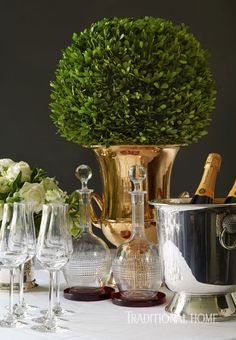 Contemporary stemware and decanters add sparkle and charm and a boxwood topiary ball tops a gold trophy vase in this charming table setting.