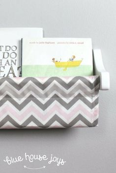 Stylish book slings in a pink and gray chevron prints to store your kids' books. Hang this up at any height and give your child a simple way to grab their favorites for a quick read. Choose from maple or white brackets. Perfect for playrooms, nurseries, a