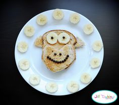 Toast 2 pieces of bread. Spread both pieces with peanut butter. Put 1 piece on your plate face up, and put the other piece face down, half way over the 1st piece. Trim the top and bottom of the 2nd piece to look like a monkey face. From the trimmed piece, cut out 2 monkey ears and place at the top of the 1st piece. Use sliced bananas and mini chocolate chips for the monkey's facial features. Add more bananas for garnish.