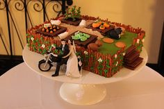 Groom's cake with a farm theme. Vanilla-almond cake, fondant & gum paste veggies and animals; pretzel fence; Kit-Kat garden beds and steps; vanilla wafer stepping stones and garden paths; Oreo garden soil.