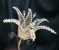 lily silver-plated made of wire tutorial.  there are other tutorials also.  site in Hungarian but translates well.  beautiful work